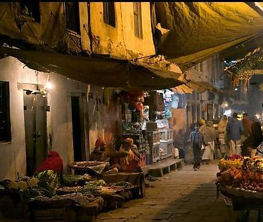 Flower vendor in narrow old city alley at night. Varanasi, Uttar Pradesh, India